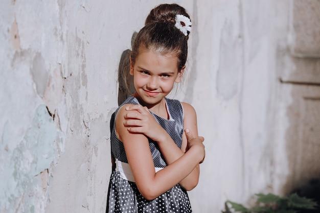 青い水玉模様のドレスを着た若いブルネットの少女は、夏に壁に立っています。高品質の写真
