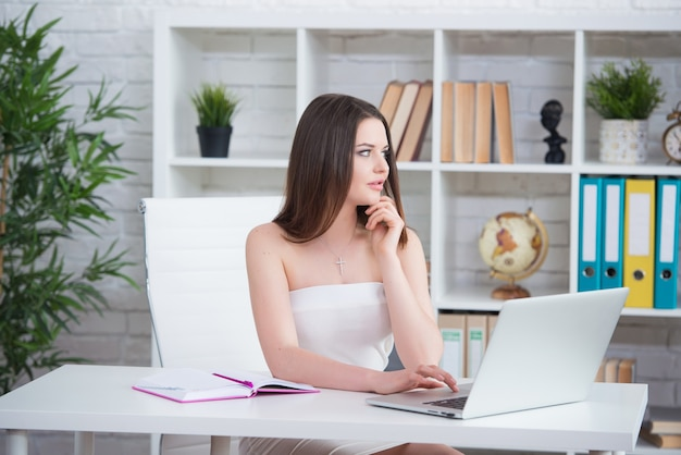 白いドレスを着た若いブルネットの少女は、テーブルのオフィスに座っています。女性はラップトップで働いています。