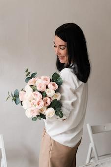白いシャツを着た若いブルネットの少女は、壁の近くで彼女の手に大きな花束を持っています