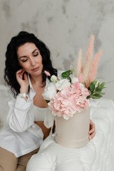 흰 셔츠에 젊은 갈색 머리 소녀는 꽃의 꽃다발 옆에 앉아