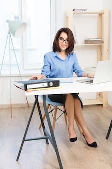 젊은 갈색 머리 여자는 사무실에서 테이블에 앉아있다. 그녀는 파란색 셔츠와 검은 색 신발을 신습니다. 그녀는 카메라에 웃고 있습니다.