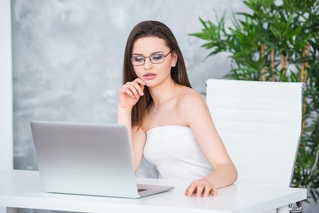 白いドレスを着た眼鏡の若いブルネットの少女は、テーブルのオフィスに座っています。女性はラップトップで働いています。ロービジョンまたはファッションアクセサリー。