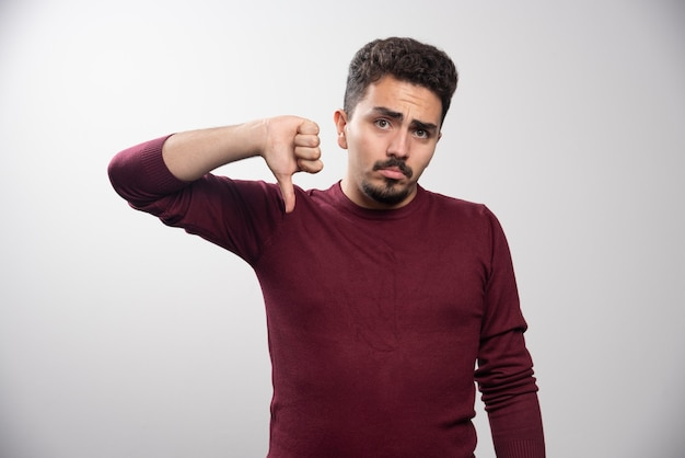 Молодой человек брюнет показывает большой палец вниз.