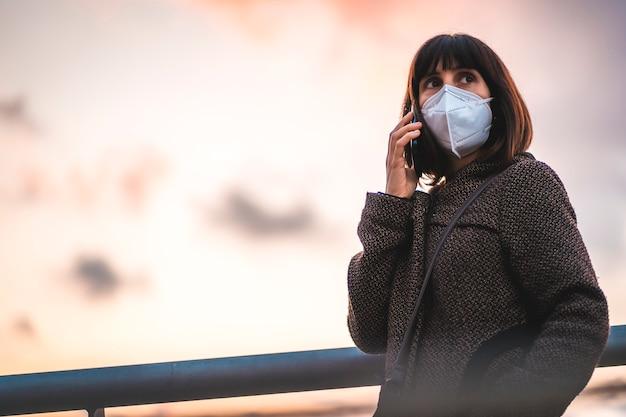 일몰에 마스크와 전화로 얘기 젊은 갈색 머리. 통제되지 않은 covid-19 전염병의 첫 걸음