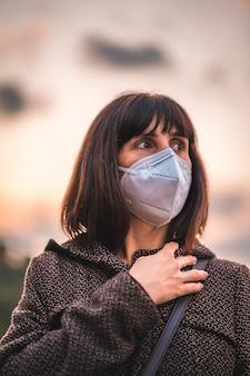 석양에 마스크와 젊은 갈색 머리. 통제되지 않은 covid-19 전염병의 첫 걸음