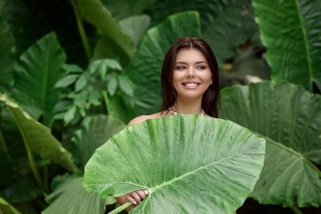 아름다운 피부와 백설 공주의 넓은 미소를 가진 젊은 갈색 머리가 큰 녹색 잎으로 포즈를 취합니다.