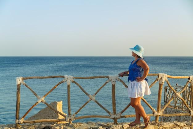 해변에서 하얀 치마를 입고 태양 모자를 쓴 젊은 갈색 머리 여성이 카메라를 반바퀴 돌면서 감탄합니다.