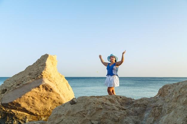 해변에 하얀 치마를 입고 태양 모자를 쓴 젊은 브루네트 여성이 바다와 하늘을 배경으로 서 있습니다.