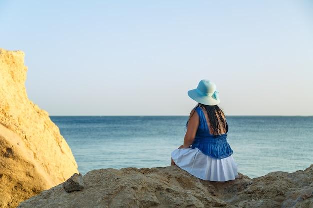 Молодая брюнетка в белой юбке и синей шляпе на берегу моря сидит на скалах спиной