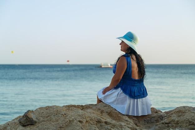 Молодая брюнетка в белой юбке и синей шляпе на берегу моря сидит спиной
