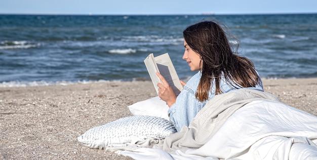 若いブルネットの女性は、毛布で覆われたビーチの海のそばに横たわって、本を読んでいます。ビーチの居心地の良い雰囲気、夏のコンセプト。