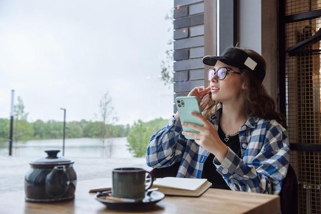 한 젊은 갈색 머리 여성이 식당의 테이블에 앉아 가제트 시계 전화기를 사용하여 인터넷에서 통신합니다.