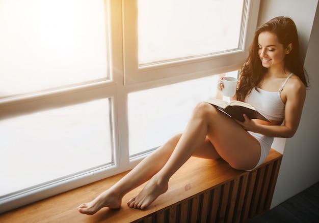 젊은 갈색 머리 여자는 창턱에 앉아 그녀의 손에 책과 차 한 잔을 들고