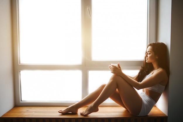 젊은 갈색 머리 여자는 창턱에 앉아 그녀의 손에 차 한잔 들고