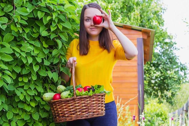 Молодая брюнетка в ярко-желтом пиджаке стоит в саду с плетеной корзиной с урожаем помидоров, зелени и цукини.