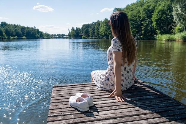 Молодая брюнетка в белом платье сидит на деревянной платформе на берегу озера