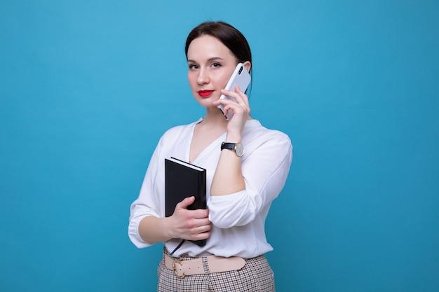 Молодая брюнетка с дневником разговаривает по телефону на синем фоне