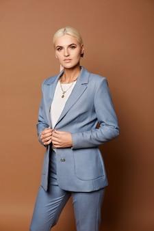 Молодая бизнес-леди с идеальными светлыми волосами и безупречным макияжем позирует в элегантном костюме на бежевом фоне. понятие деловой моды и красоты