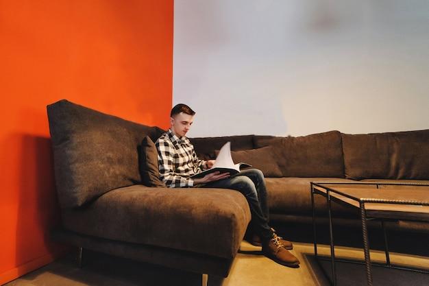 Молодой деловой человек читает бизнес-проект в стильном офисе. отдых с журналом.