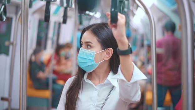 Молодая деловая женщина носит маску для лица в общественном транспорте, безопасное путешествие, концепция защиты от covid-19.