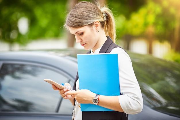 手に書類用のフォルダーを持っている若いビジネスウーマンは、彼女のスマートフォンを見ています。
