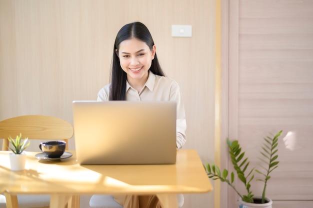 커피 숍에서 그녀의 노트북을 사용하는 젊은 비즈니스 우먼