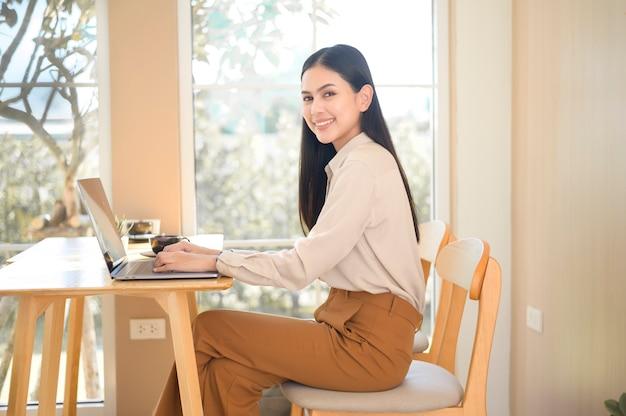 コーヒーショップで彼女のラップトップで働いている若いビジネスウーマン