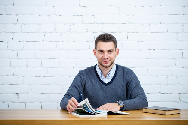 Молодой бизнесмен сидит за столом с книгой