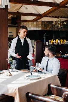 Молодой бизнесмен в прекрасном ресторане рассматривает меню и делает заказ молодому официанту в стильном фартуке. обслуживание клиентов.