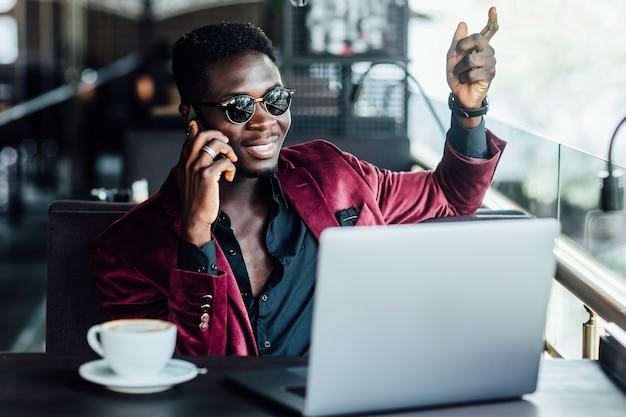 Молодой бизнесмен сидит в кафе с ноутбуком и телефоном в руке, на столе стоят и кофе.