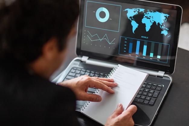 青年実業家は、コンピューター上のグラフとノートパソコンに取り組んでいます。