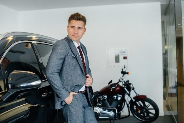 若いビジネスマンが自動車販売店で新車を見ています。車を買う。