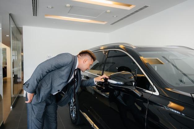Молодой бизнесмен смотрит на новую машину в автосалоне. покупка машины.