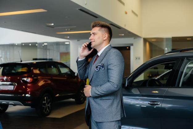 젊은 사업가가 새 차를 구입 한 후 전화를 겁니다.