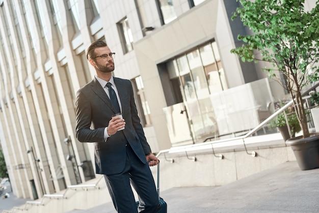 안경을 쓴 젊은 사업가가 커피와 여행 가방을 들고 계단을 오른다