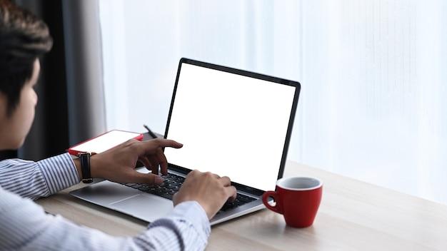 コンピューターのラップトップを使用し、インターネットで情報を探している青年実業家。