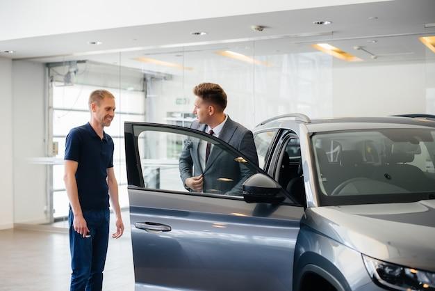 Молодой бизнесмен с продавцом рассматривают новую машину в автосалоне. покупка машины.
