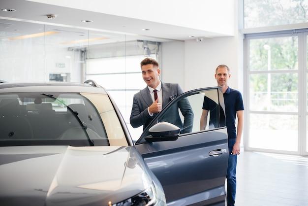セールスマンのいる青年実業家が、自動車販売店で新車を見ています。車を買う。