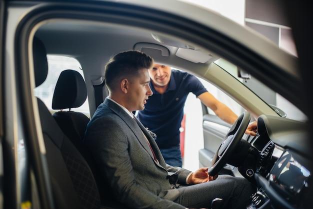 Молодой бизнесмен с продавцом смотрит на новую машину в автосалоне. покупка машины.