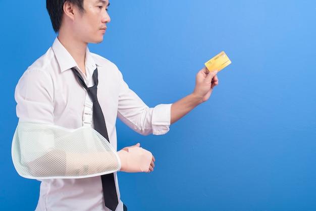 Молодой бизнесмен с травмированной рукой в перевязи, держащей кредитную карту или карту медицинского страхования на синем фоне в концепции студии, страхования и здравоохранения