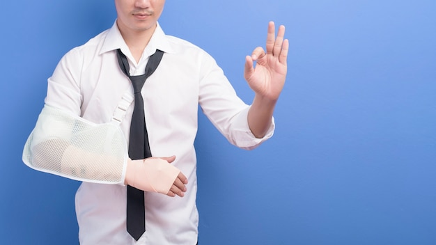 Молодой бизнесмен с травмированной рукой в перевязке через синюю стену, страхование и концепцию здравоохранения
