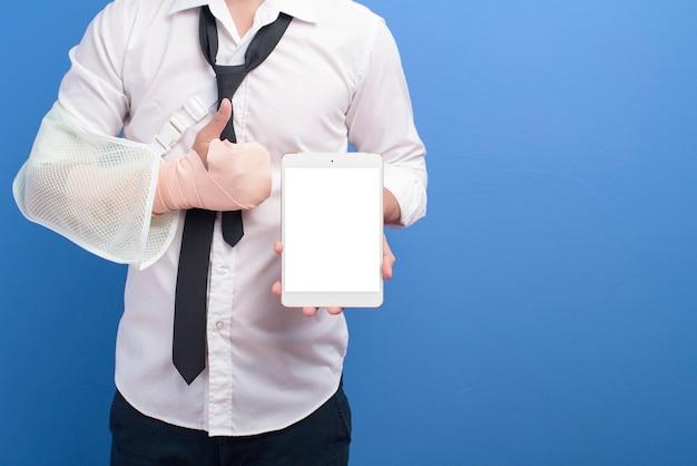 Молодой бизнесмен с травмированной рукой в перевязке, используя планшет на синем фоне в студии, страховании и концепции здравоохранения