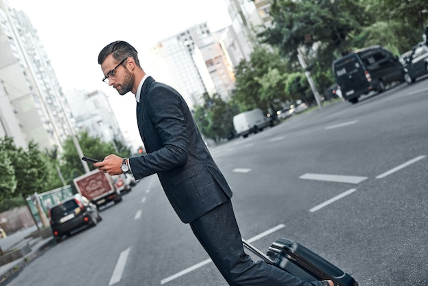 안경을 쓴 젊은 사업가가 스마트폰으로 채팅을 하고 길을 건너고 있다