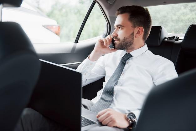랩톱에서 작업하고 차 뒤쪽에 앉아있는 동안 전화로 얘기하는 젊은 사업가. 운동, 시간을 주셔서 감사합니다