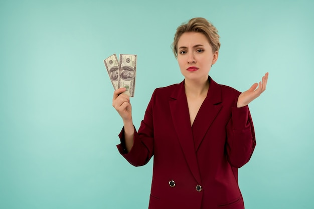 Оставшиеся деньги молодая бизнесвумен-банкрот держит в руках оставшиеся деньги. подавленное состояние в день выплаты кредита. на синем фоне с copyspase