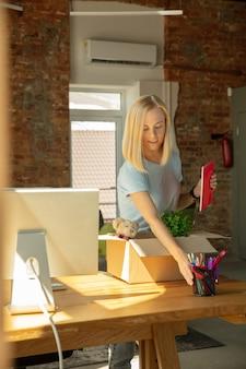새로운 작업 장소를 점점 사무실에서 이동 젊은 사업가. 젊은 백인 여성 회사원 승진 후 새 캐비닛 장비