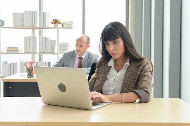 뒤에 동료와 함께 현대 사무실에서 노트북으로 작업하는 젊은 여성 사업가
