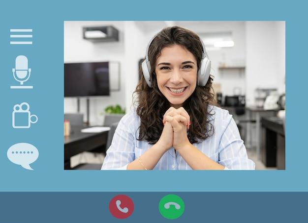 ノートパソコンを使用している若い実業家が、自宅で仕事をしているときに、ビデオ通話の会議で同僚に計画について話します。