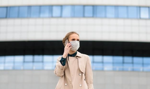 健康マスクを着用し、市内の電話で話している若い実業家