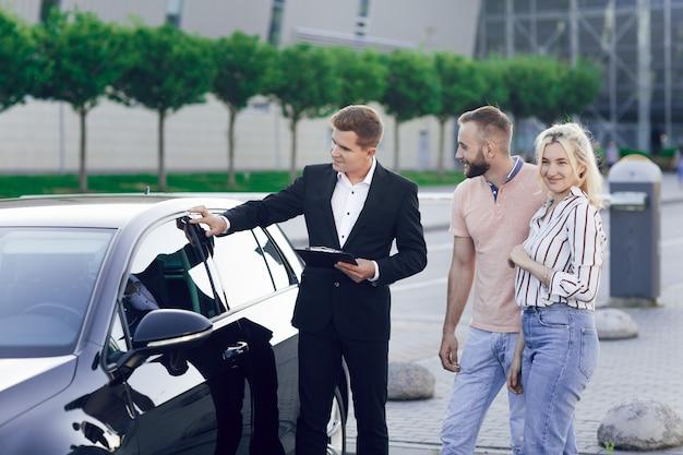 ビジネススーツを着た若い自動車ディーラーは、買い手に新しい車を見せます。若いカップル、男性と女性、車を購入します。機械の購入、試乗。